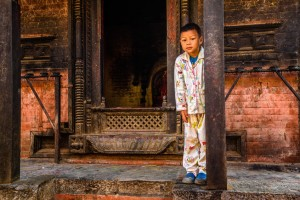 Small boy in pajamas stands in front of his home